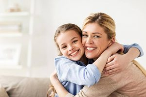 mother and daughter smiling and embracing