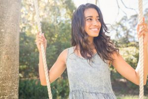 Young woman smiling on a swing set outdoors