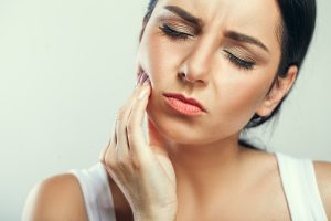 Woman with TMJ grasping her cheek