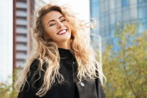Young woman with a perfect smile with a city scape behind her